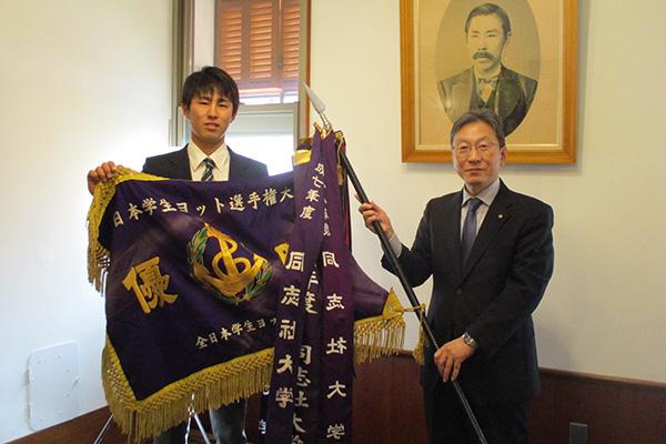 杉山前主将から学長へ総合優勝旗を手渡す